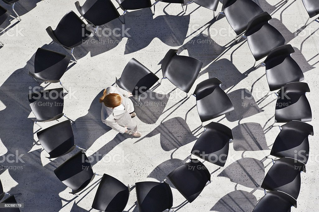 Woman standing in spiral of office chairs stock photo
