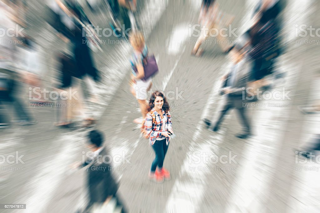 Woman standing in the middle of crowd crossing street stock photo