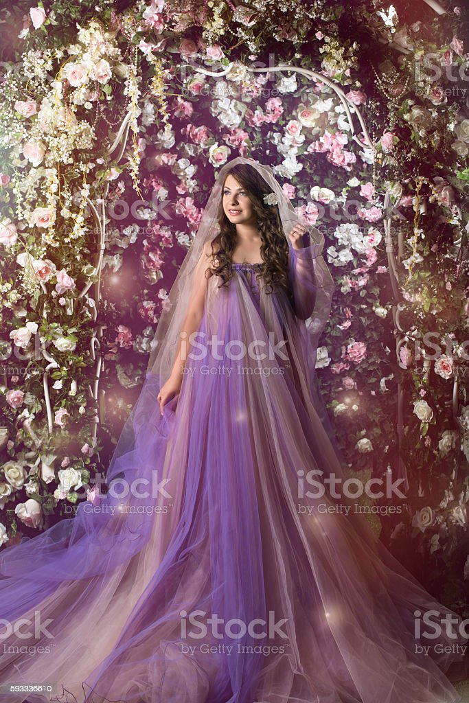 woman standing in violet long dress under arch stock photo