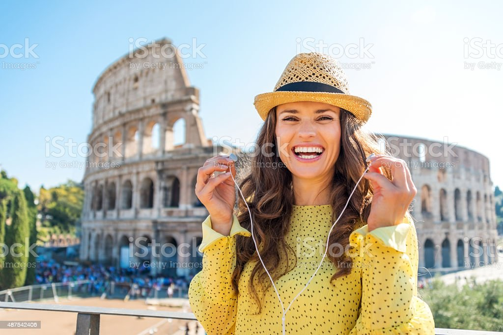 Woman standing near Colosseum in Rome removing earbuds stock photo