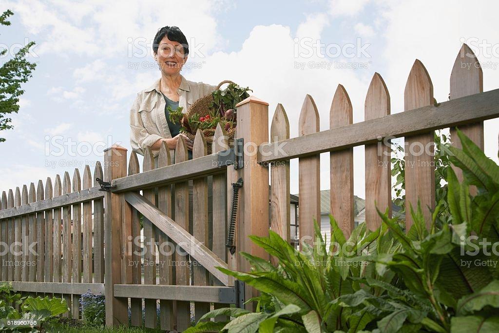 Woman standing near gate stock photo