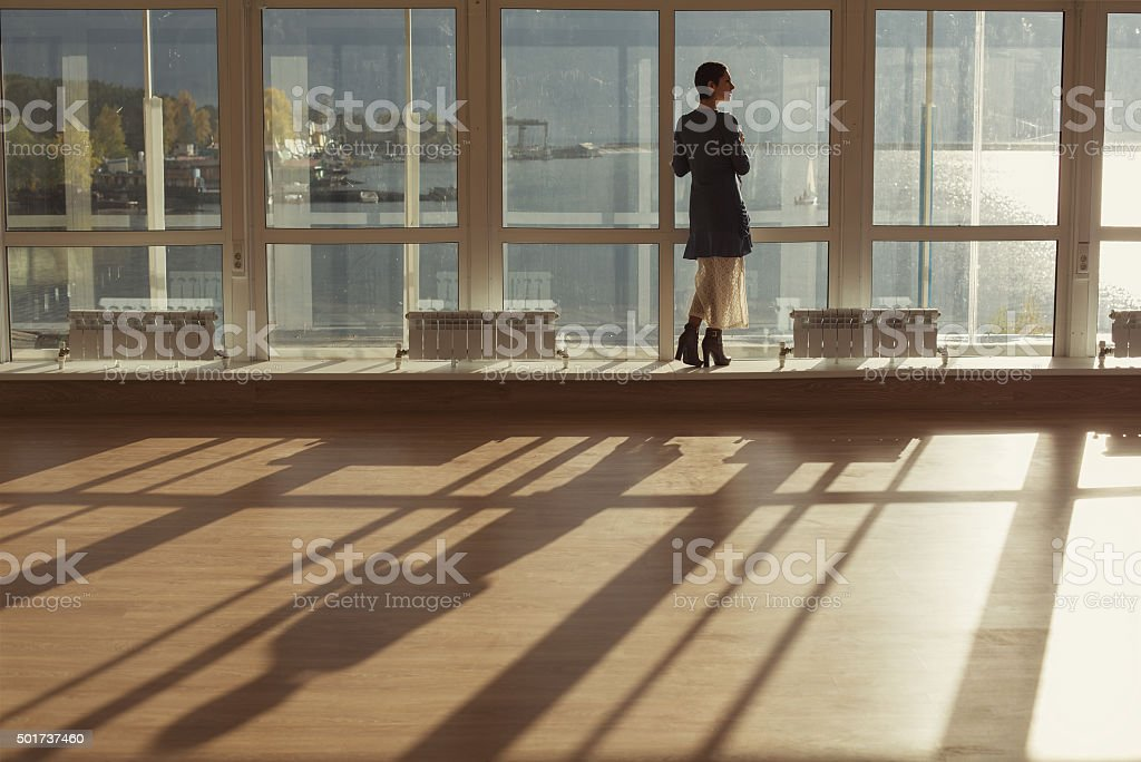 Woman standing near large window and looking to sunset stock photo
