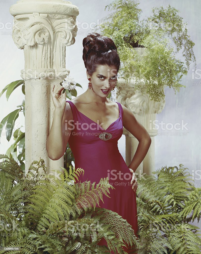 Woman standing near pedestal and plants, portrait royalty-free stock photo