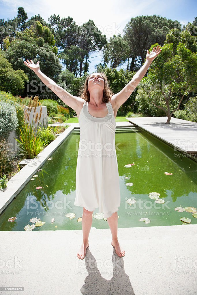 Woman standing near swimming pool with arms raised stock photo