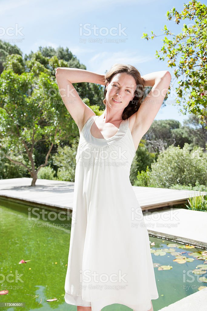 Woman standing near swimming pool with hands behind head stock photo