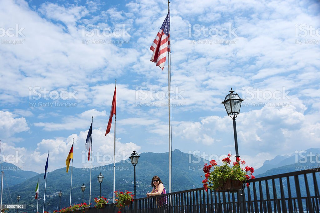 Woman standing next railing with several national flags -XXXL royalty-free stock photo
