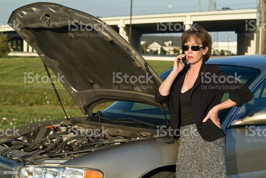 Woman standing next to open car hood calling for help stock photo