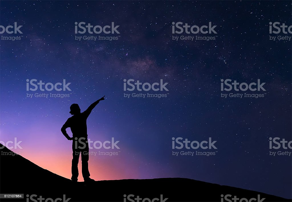Woman standing next to the milky way and pointing stars stock photo