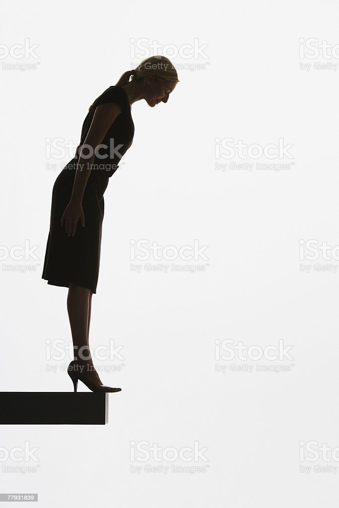Woman standing on a plank looking over ledge stock photo