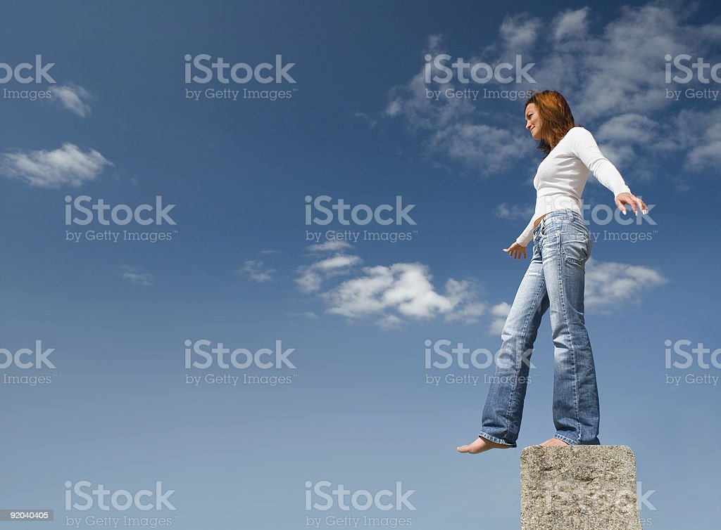 Woman standing on a tall concrete stone stock photo