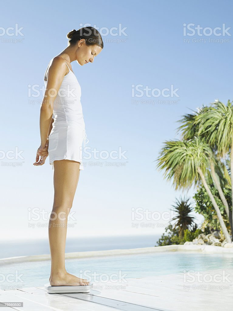 Woman standing on a weight scale royalty-free stock photo