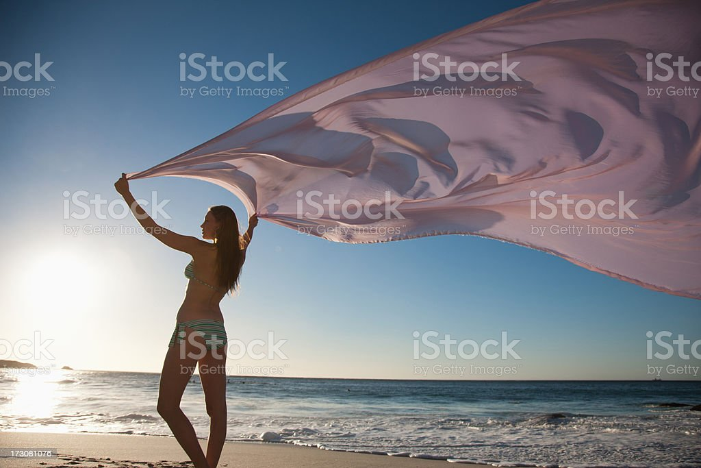 Woman standing on beach with fabric royalty-free stock photo