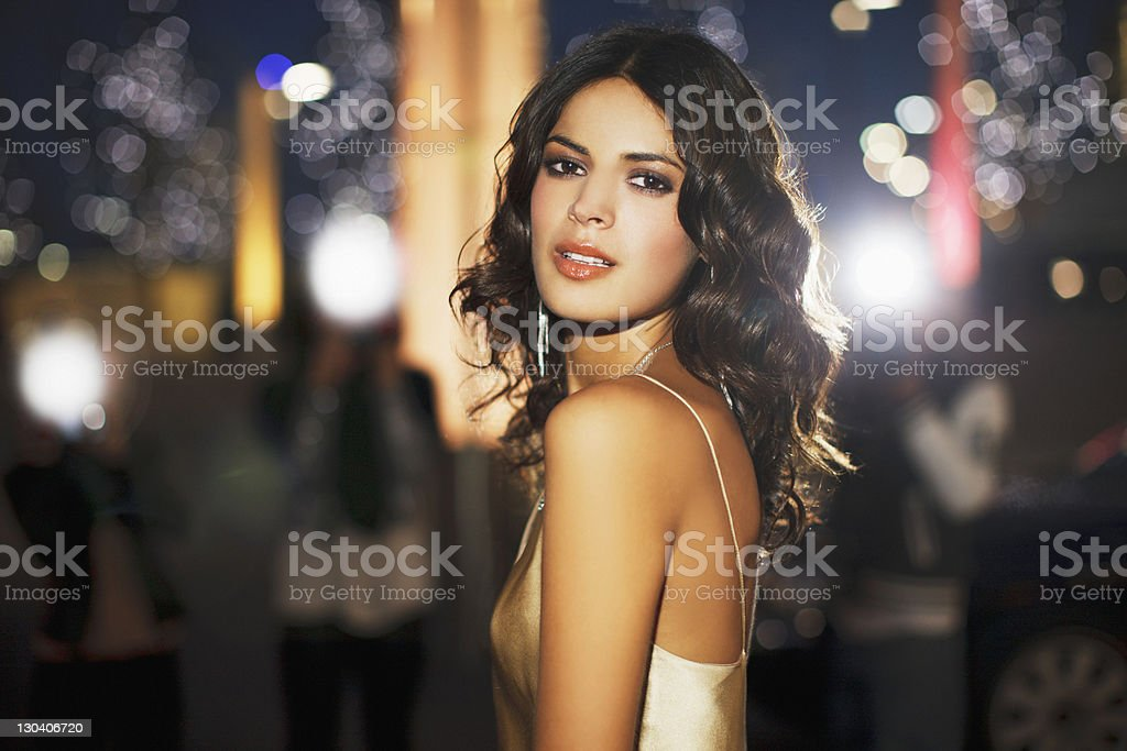 Woman standing on city street at night stock photo