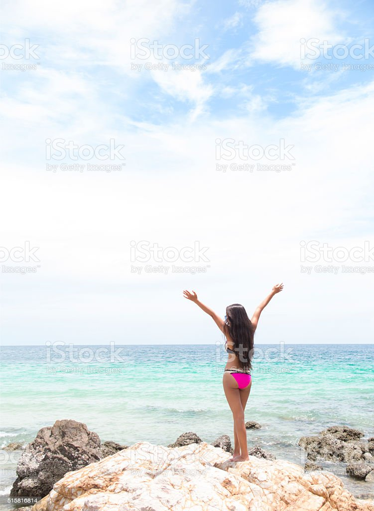 Woman standing on coastal rocks with arms raised. stock photo