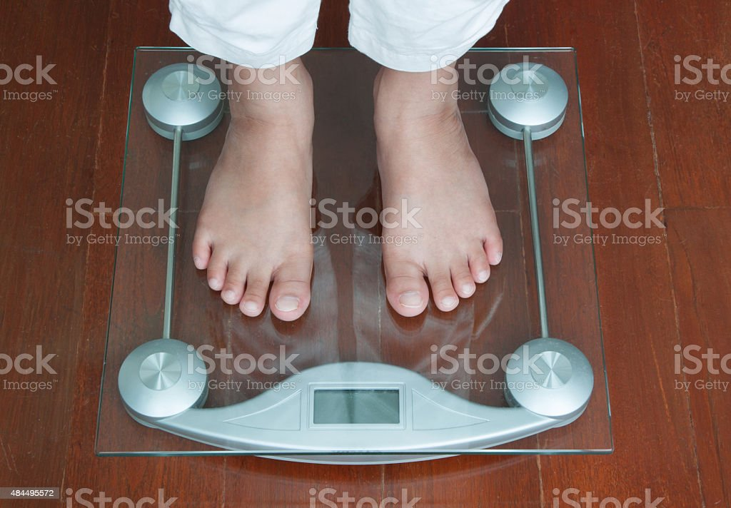 Woman Standing on Digital Weighing Apparatus stock photo
