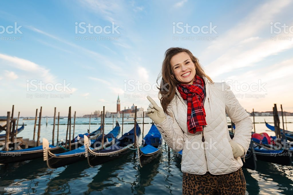 Woman standing on embankment and pointing, Venice stock photo