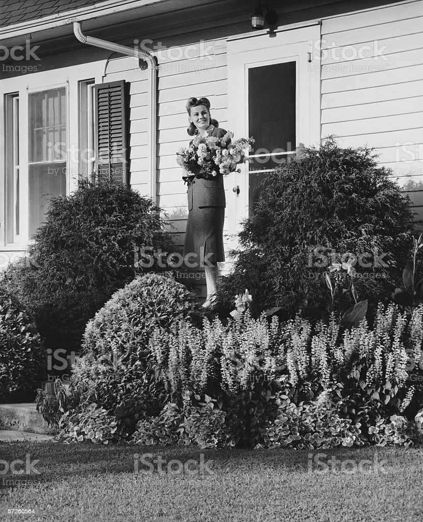 Woman standing on front porch of house holding bunch of flowers, (B&W) stock photo