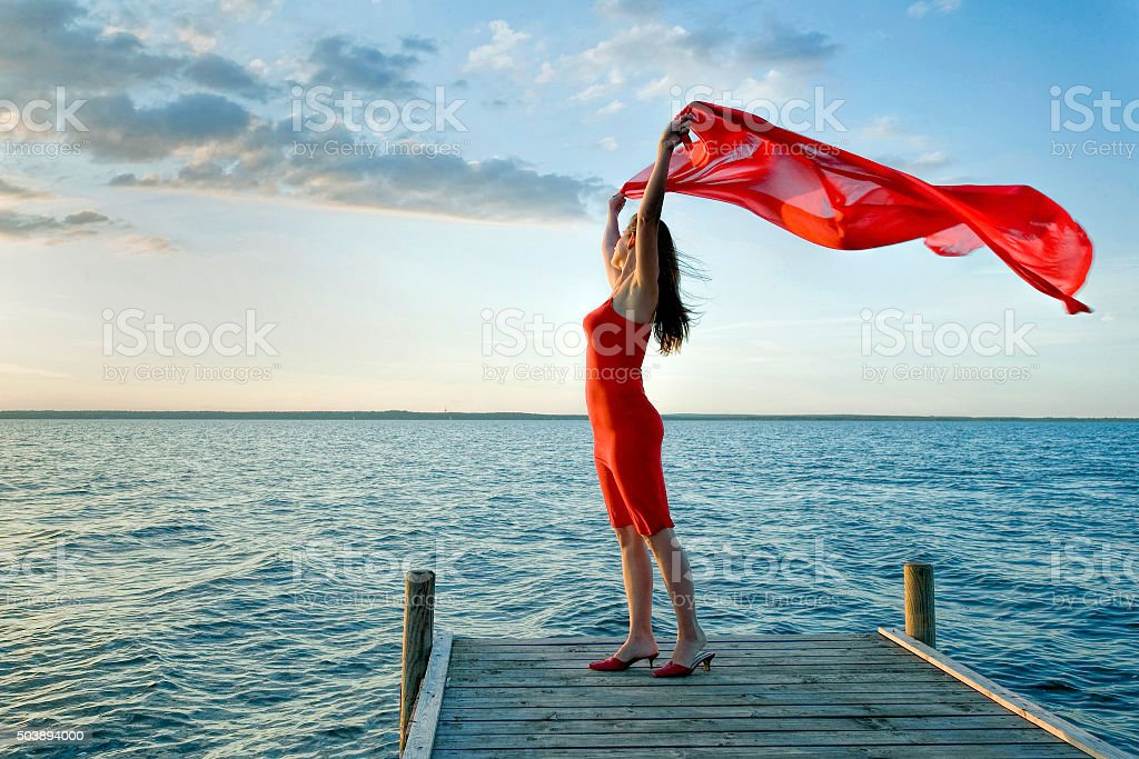 Woman standing on lakeside jetty holding red scarf to wind stock photo