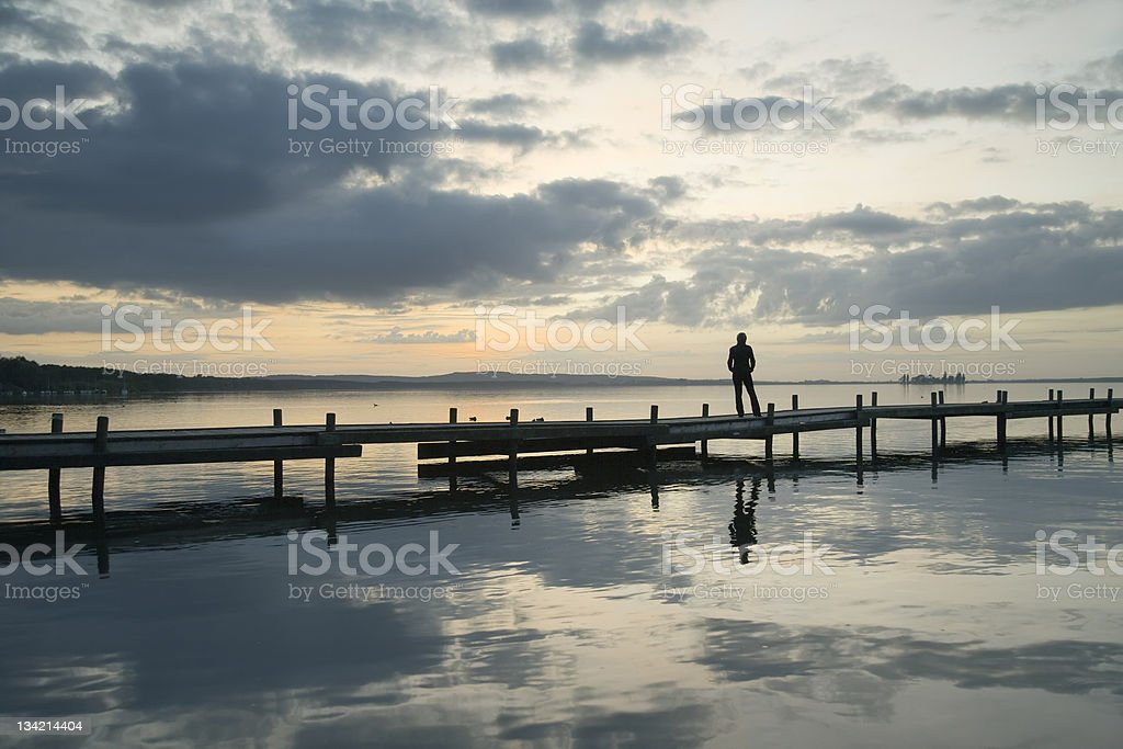 Woman standing on lakeside jetty watching majestic cloudscape at dusk royalty-free stock photo
