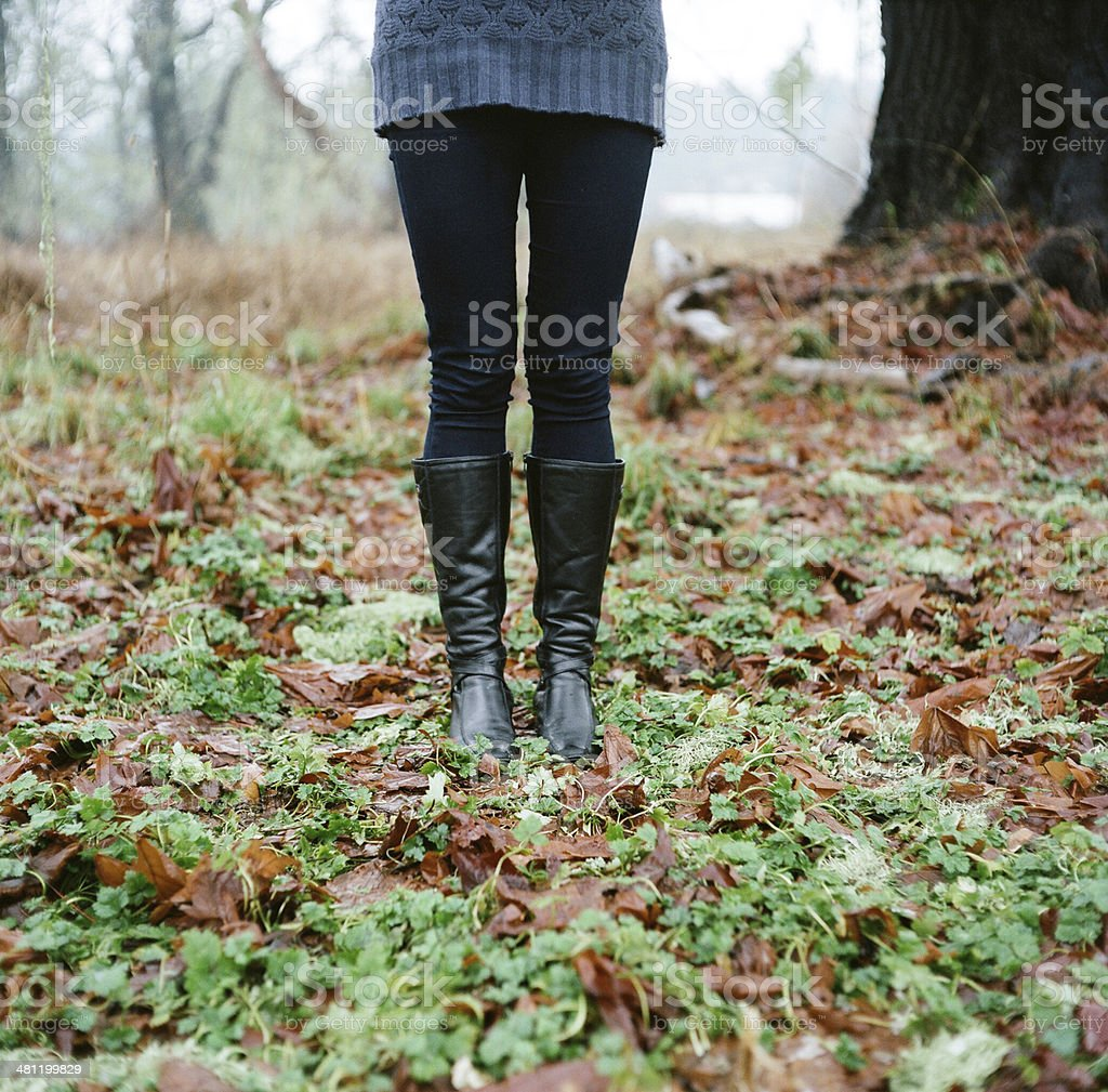 Woman standing on mossy ground with leaves stock photo
