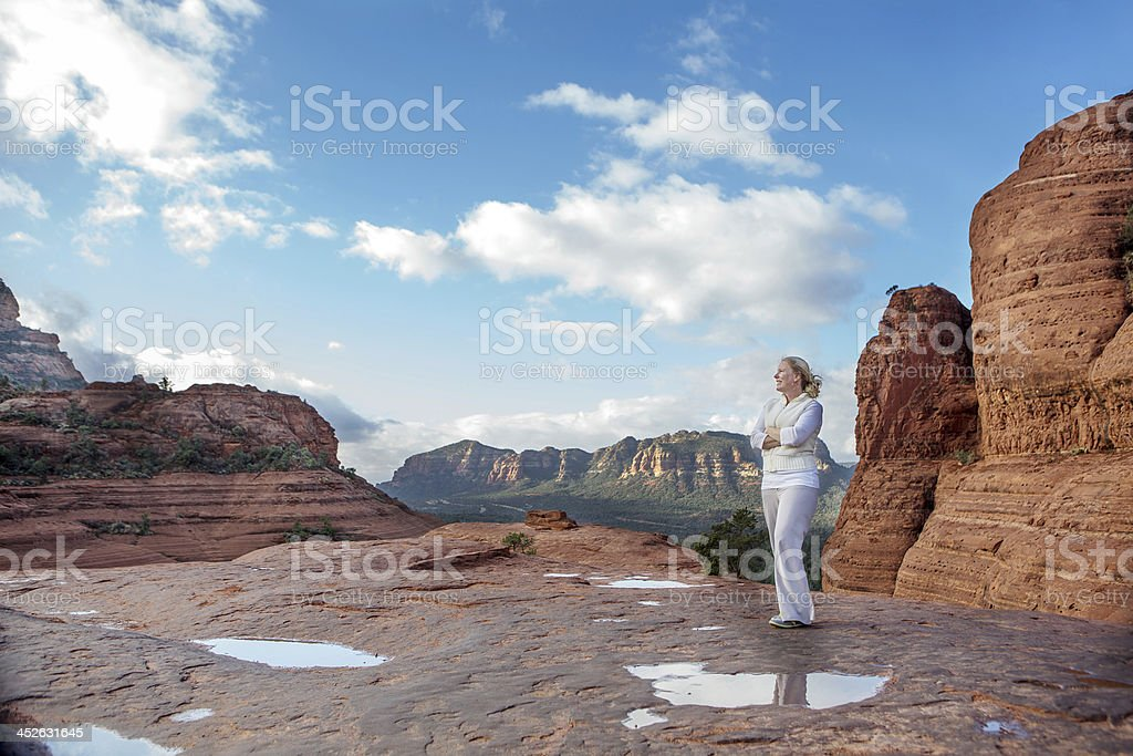 Woman standing on red rocks stock photo