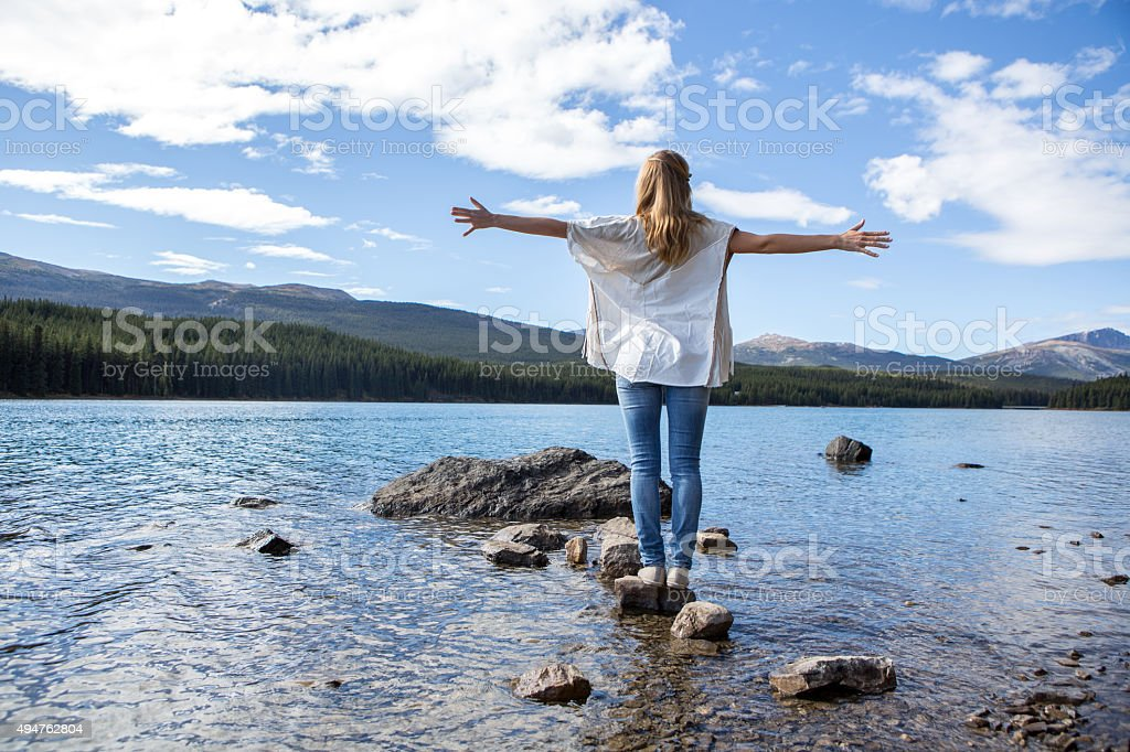Woman standing on rock above lake arms outstretched stock photo