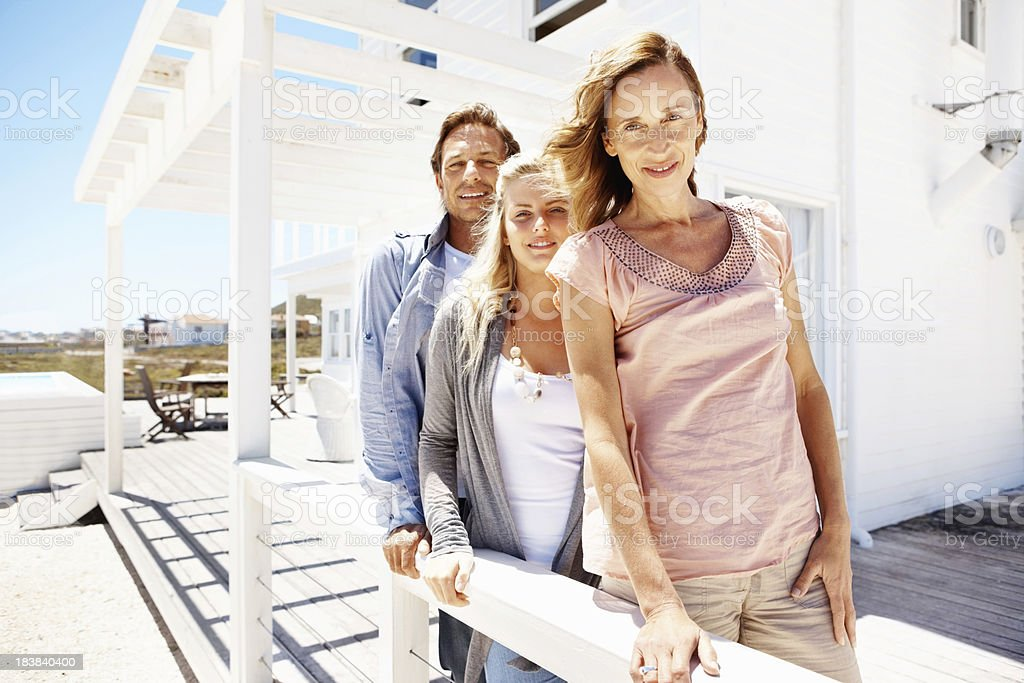 Woman standing on the porch with her husband and daughter royalty-free stock photo