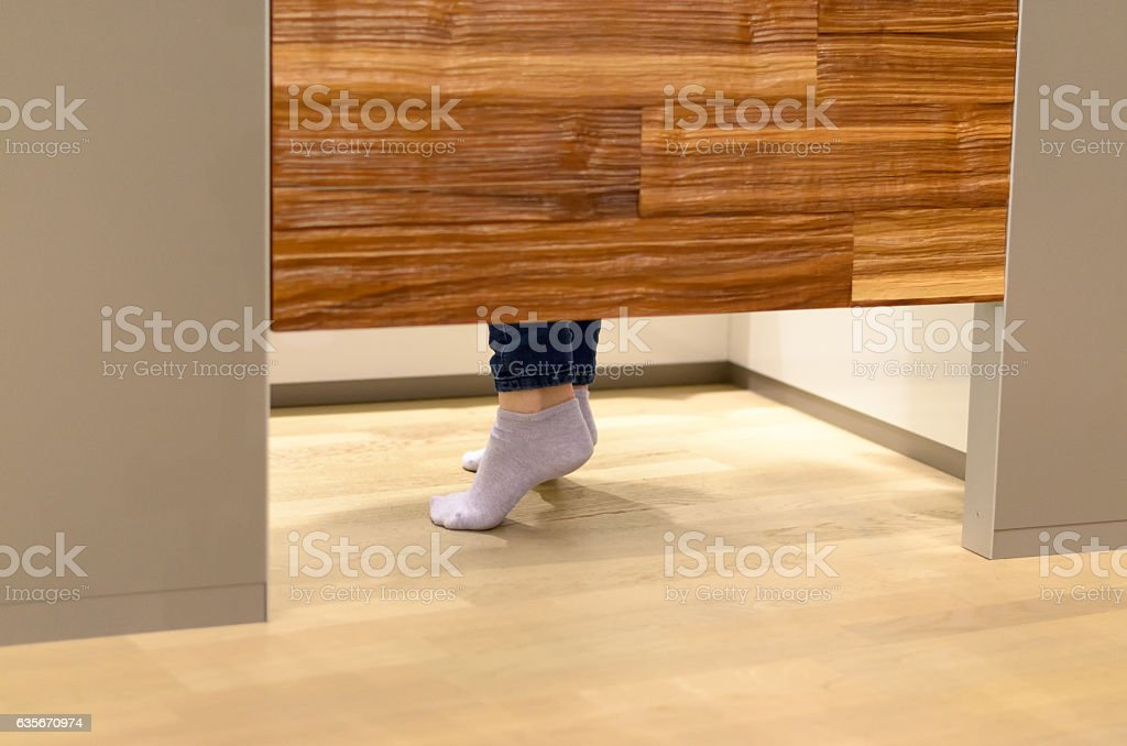 Woman standing on tip toe in a changing room stock photo