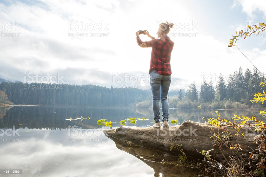 Woman standing on tree log photographing landscape stock photo