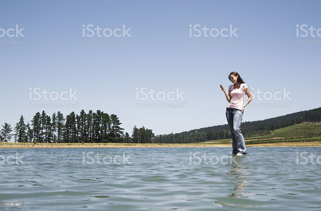 Woman standing on water with cell phone royalty-free stock photo