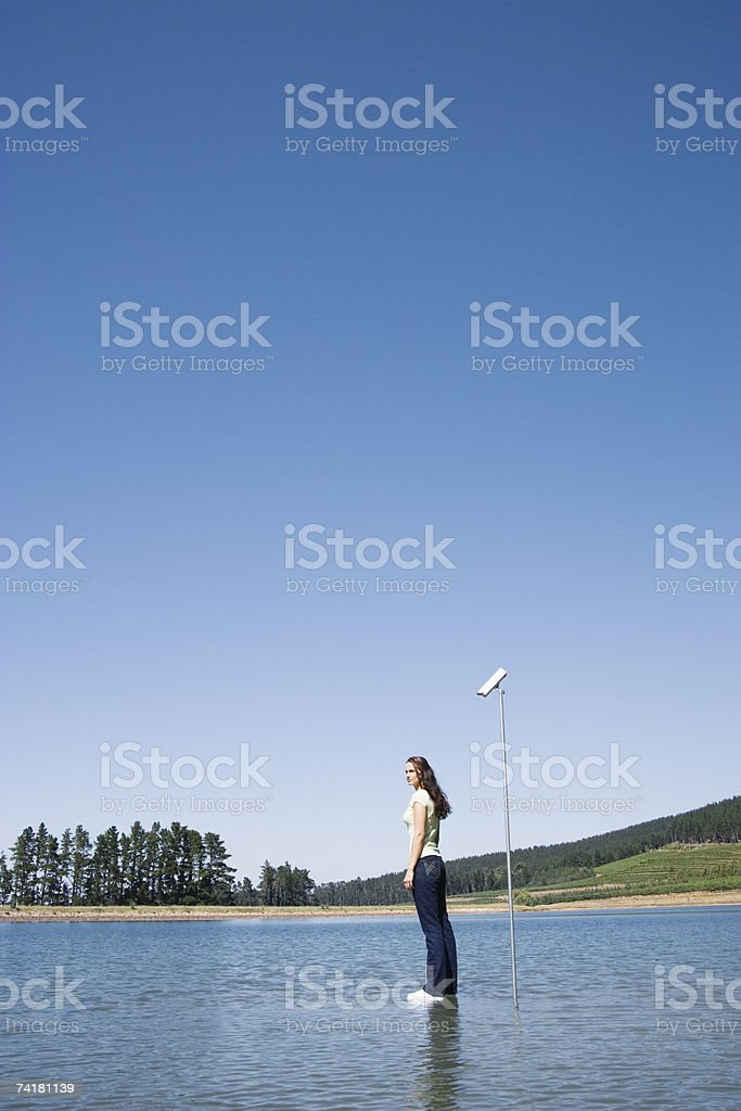 Woman standing on water with surveillance camera and trees royalty-free stock photo