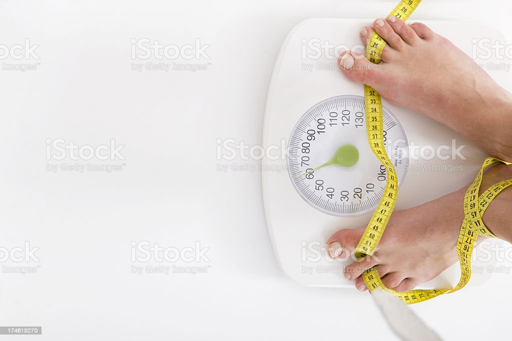 Woman standing on weight scale stock photo