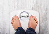 Woman standing on weight scale showing error message