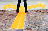 Woman standing on yellow direction arrow