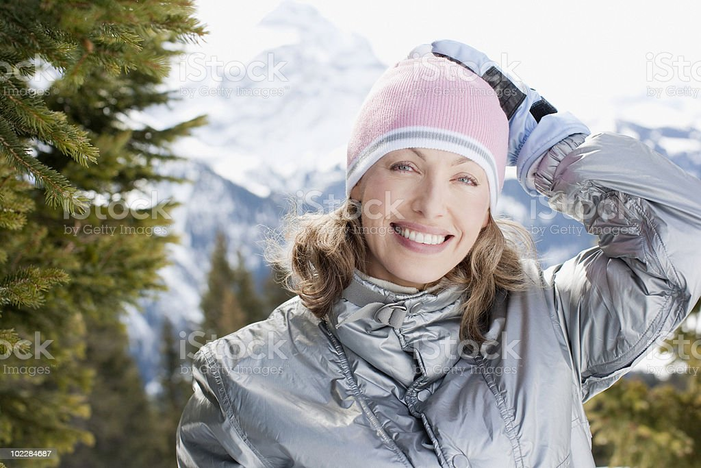Woman standing outdoors in coat and cap royalty-free stock photo
