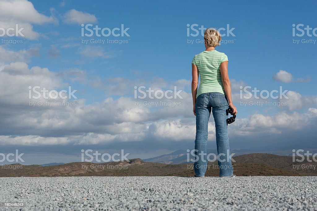 Woman standing outdoors with binocular royalty-free stock photo