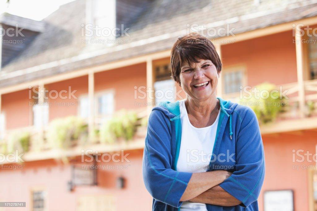 Woman standing outside building in sweatshirt stock photo