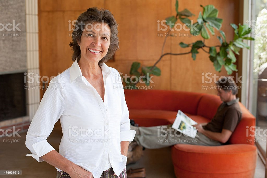 Woman standing smiling in modern home stock photo