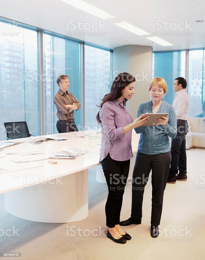 Woman standing together to discuss plans on tablet computer stock photo