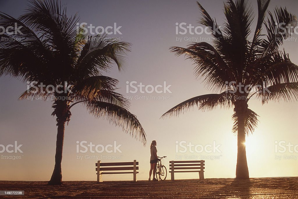 Woman standing with bicycle by palm trees stock photo