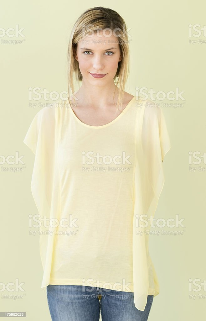 Woman Standing With Hands Behind Back Against Green Background royalty-free stock photo