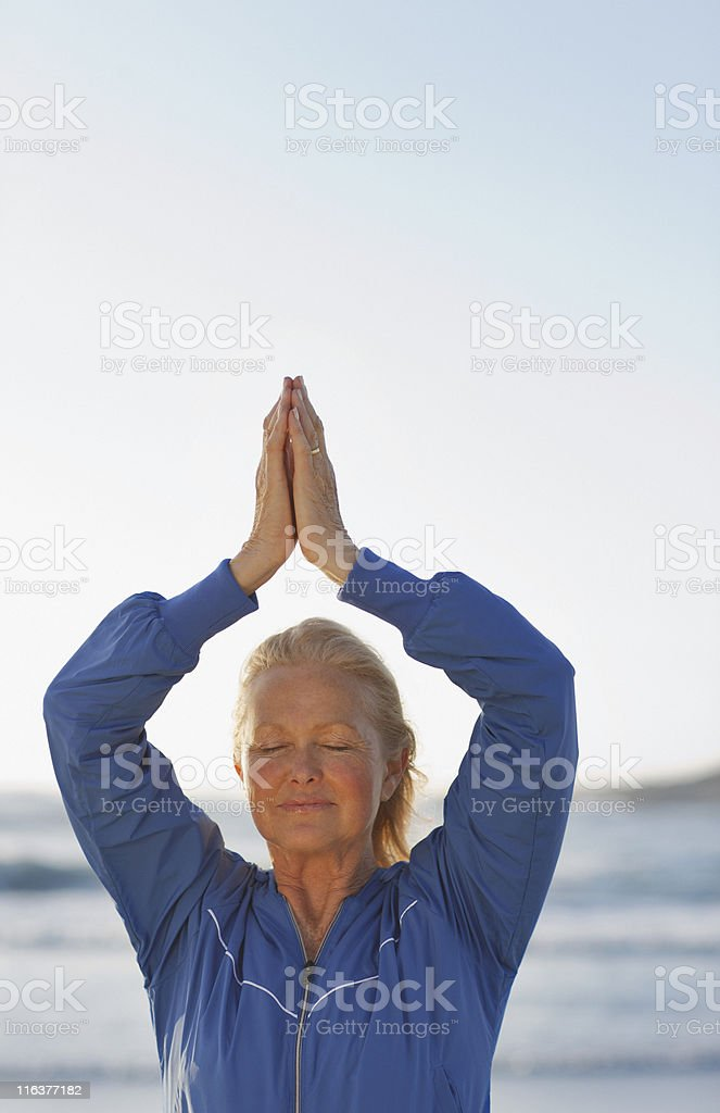 Woman standing with hands clasped overhead stock photo