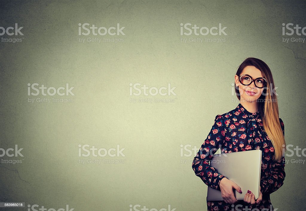 Woman standing with laptop over gray wall background stock photo