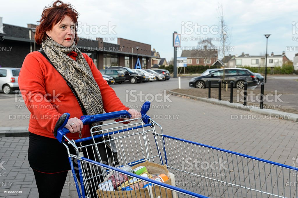 Woman standing with shopping cart outside on the parking stock photo