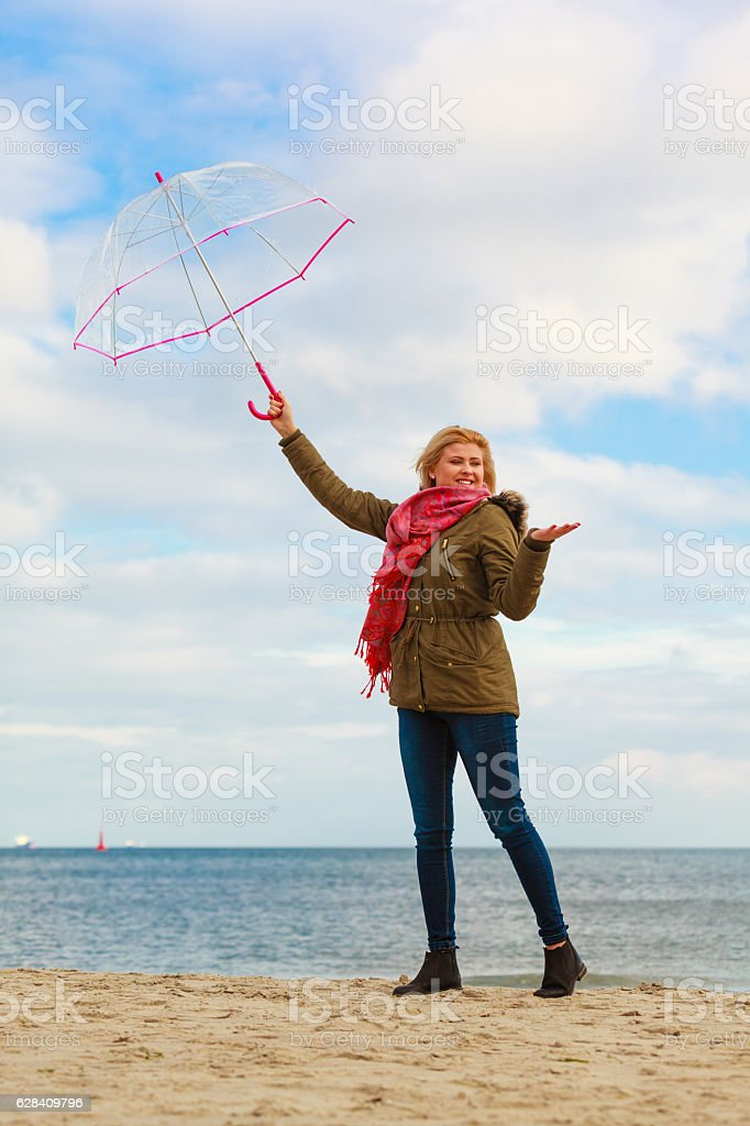 Woman standing with transparent umbrella on beach stock photo