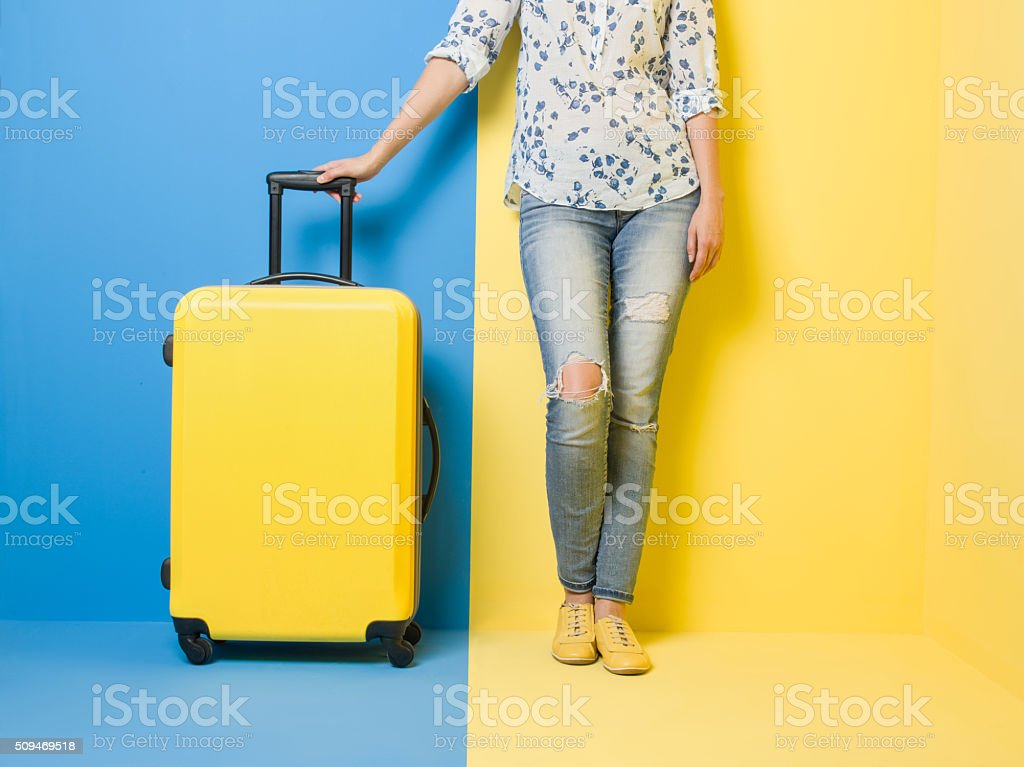 Woman stands beside suitcase stock photo