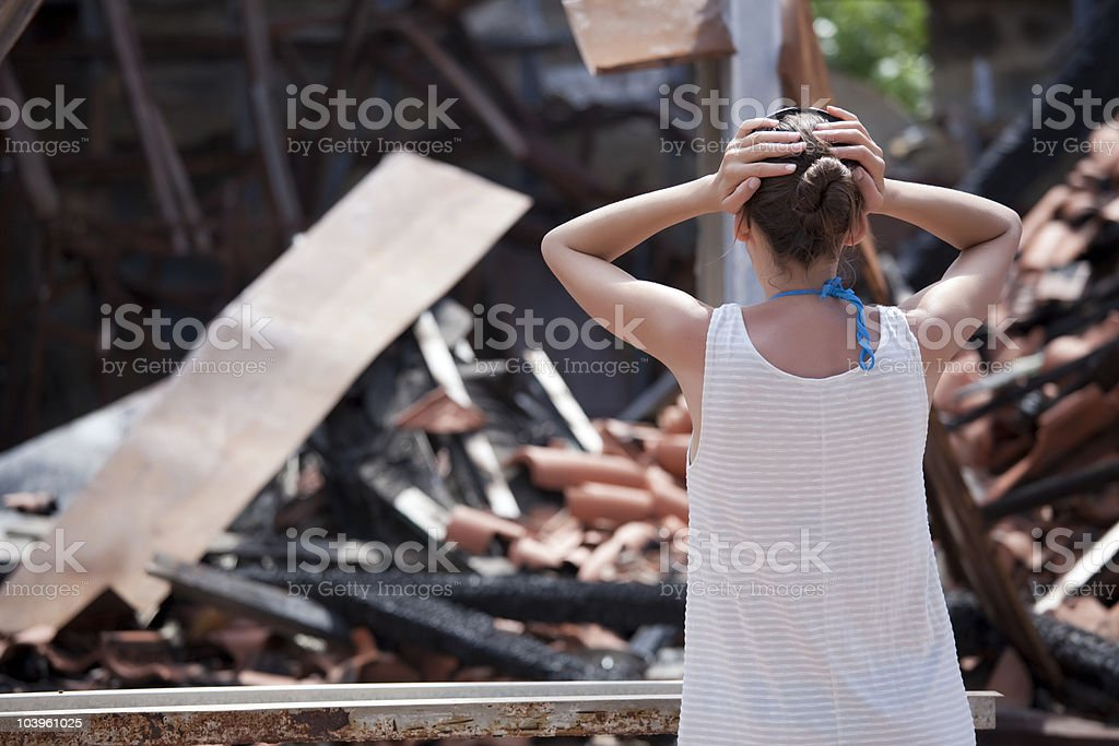 woman stands in front of burned out house stock photo