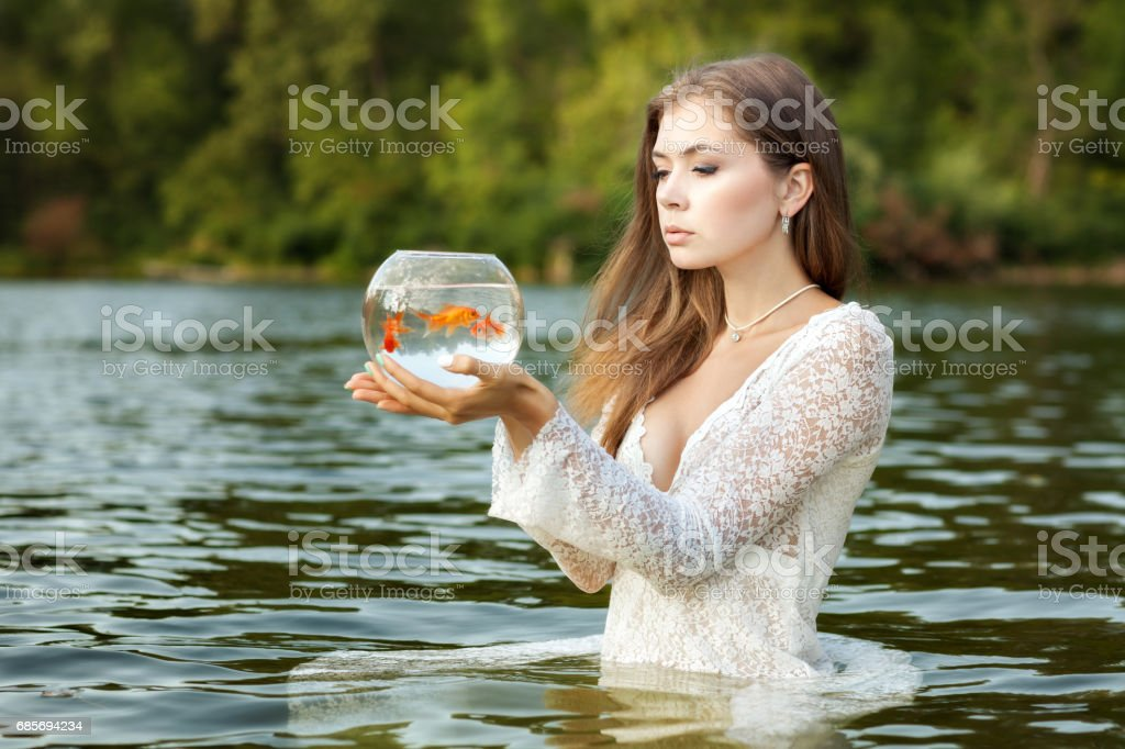 Woman stands in water, hands of an aquarium. stock photo