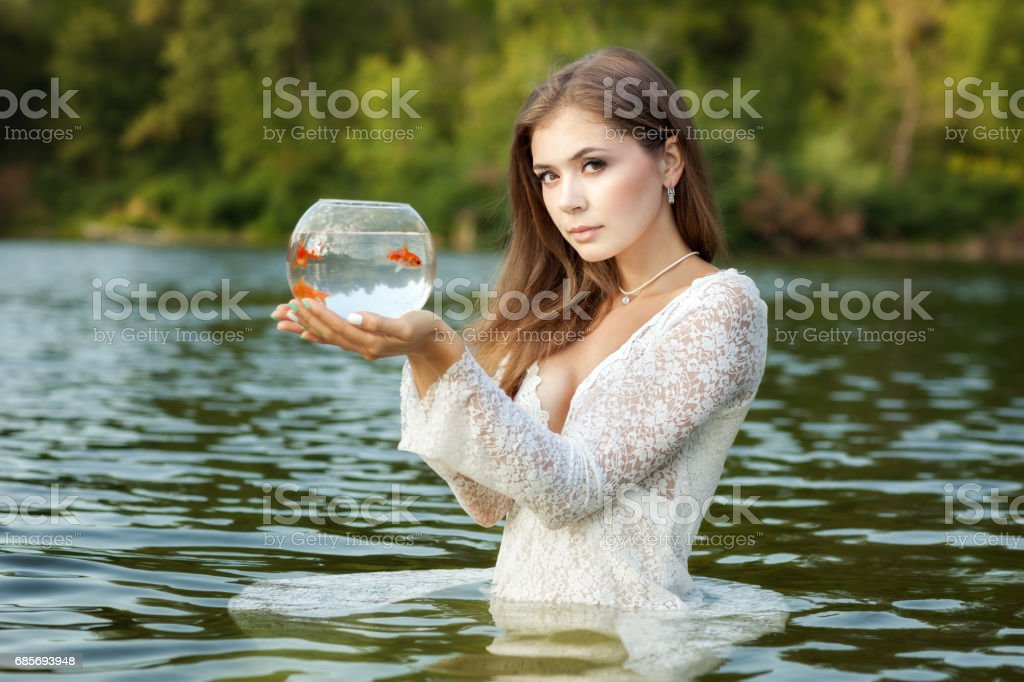 Woman stands in water, in her hands a goldfish. stock photo