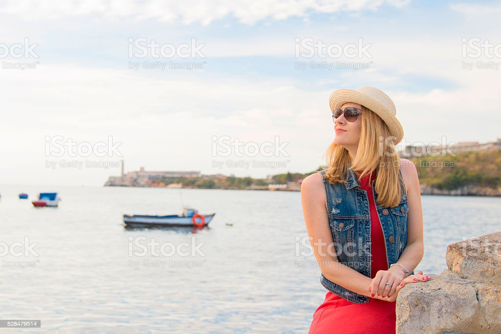 Woman stands near see with Morro castle at background stock photo